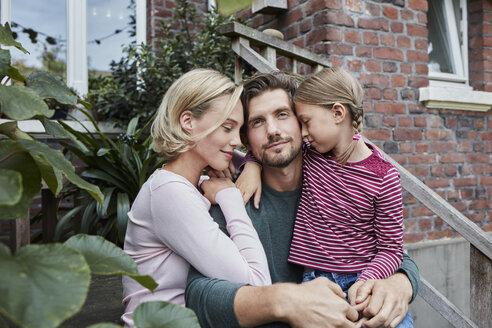 Deutschland, Nordrhein-Westfalen, Stadt Essen, Familie, Lifestyle, Familie sitzt auf der Veranda-Treppe, Kuscheln, Haus, Immobilie - RORF01646