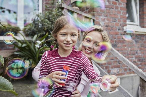 Deutschland, Nordrhein-Westfalen, Stadt Essen, Familie, Lifestyle, Mutter und Tochter spielen mit Seifenblasen, Veranda, Haus, Immobilie, Backsteingebaeude - RORF01652