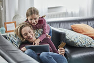 Happy mother and daughter shopping online on couch at home - RORF01655