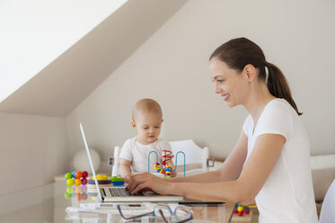 Smiling mother using laptop and little daughter playing at table at home - DIGF05613