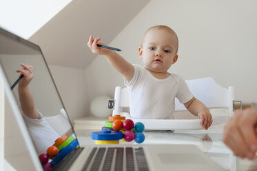 Little daughter playing and mother using laptop at table at home - DIGF05625