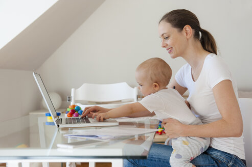 Smiling mother and little daughter using laptop together at table at home - DIGF05628