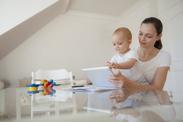 Mother and little daughter using tablet together at home - DIGF05631