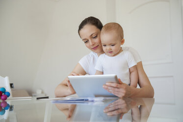 Mother and little daughter using tablet together at home - DIGF05634