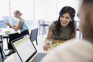 Smiling businesswoman using laptop with coworker eating lunch in office cafeteria - HEROF05897