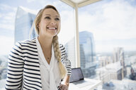 Smiling businesswoman at urban office window - HEROF05900