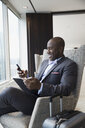Smiling businessman with luggage using cell phone and digital tablet in airport lounge - HEROF05903