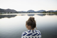Serene young woman in sweater at lake at dusk - HEROF05921