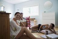 Portrait smiling mother and daughters relaxing in bedroom - HEROF05936