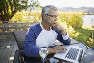 Senior man drinking white wine and using laptop at lakeside patio - HEROF05939