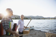 Retired couple carrying picnic basket and blanket on sunny summer lake beach - HEROF05945