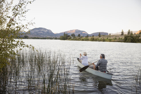 Retired couple canoeing on tranquil lake - HEROF05951