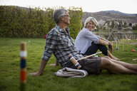 Retired couple playing croquet relaxing in summer grass - HEROF05954