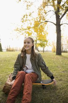 Portrait smiling tween girl on skateboard at autumn park - HEROF06032