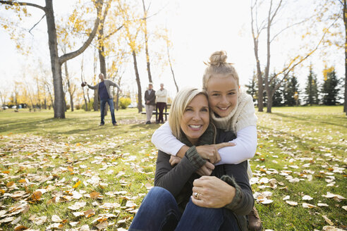 Portrait smiling mother and daughter hugging in sunny autumn park - HEROF06041