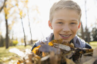 Portrait smiling tween boy with braces holding autumn leaves in sunny park - HEROF06044