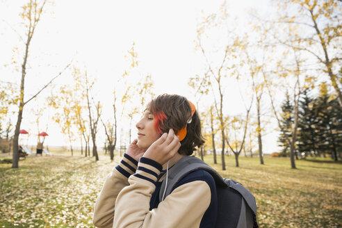 Serene tween boy listening to music with headphones in autumn park - HEROF06047
