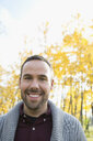 Portrait smiling man with beard in autumn woods - HEROF06074