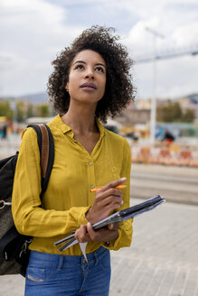 Afro woman in yellow shirt in the city. Barcelona, Spain. - MAUF02329