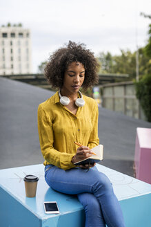 Woman sitting on bench with smartphone and coffee to go writing in notebook - MAUF02335