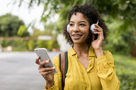 Portrait of smiling woman listening music with headphones and smartphone outdoors - MAUF02341