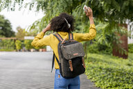 Back view of woman with backpack listening music with headphones and smartphone outdoors - MAUF02344