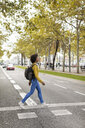 Woman with backpack crossing the street - MAUF02353