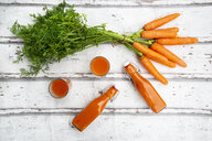 Carrots, glasses of carrot juice and swing top bottles on wood, from above - LVF07659