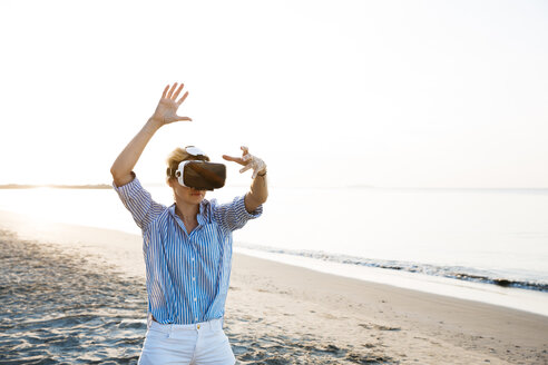 Blonde woman doing kind of yoga exercises on a beach in thailand with 3D virtual reality goggles - HMEF00177