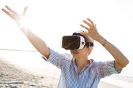 Blonde woman doing kind of yoga exercises on a beach in thailand with 3D virtual reality goggles - HMEF00180