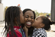 Affectionate daughters kissing mother - HEROF06134