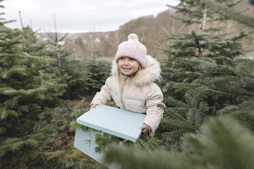Happy girl carrying gift box on a Christmas tree plantation - KMKF00737