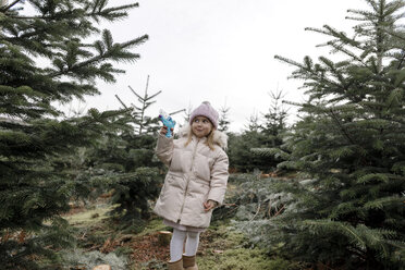 Happy girl playing with water gun on a Christmas tree plantation - KMKF00740