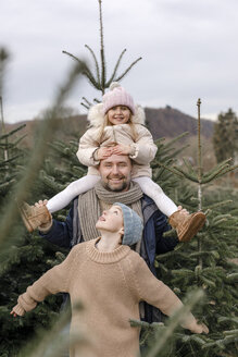 Portrait of happy father with two children on a Christmas tree plantation - KMKF00743