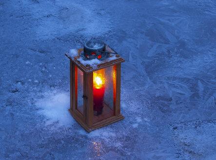 Burning lantern on ice at blue hour - WWF04877