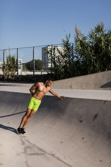 Barechested muscular man exercising in a skatepark - MAUF02377