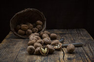Whole and cracked walnuts, nutcracker and wickerbasket on wood - LVF07669