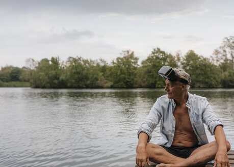 Senior man sitting on jetty at a lake wearing VR glasses - GUSF01785