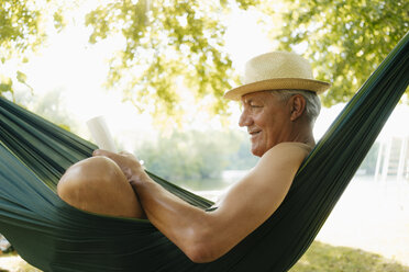 Senior man wearing straw hat relaxing in hammock at lakeshore reading book - GUSF01788