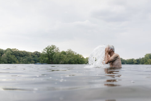Senior man in a lake splashing water in his face - GUSF01791