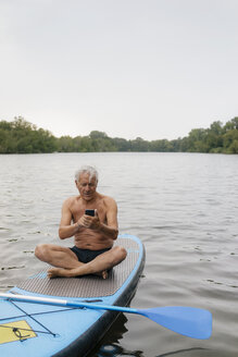Senior man sitting on SUP board on a lake using cell phone - GUSF01803