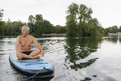 Senior man sitting on SUP board on a lake - GUSF01809