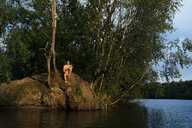 Man sitting on an island in a lake - GUSF01812