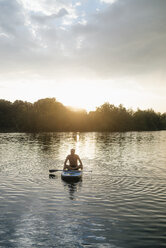 Senior man sitting on SUP board at sunset - GUSF01815