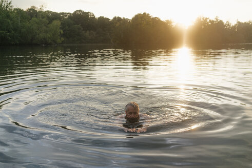 Senior man swimming in a lake at sunset - GUSF01818