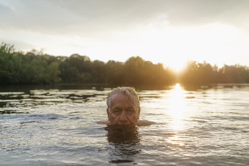 Senior man swimming in a lake at sunset - GUSF01821