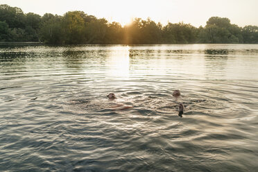 Old and young man swimming in a lake at sunset - GUSF01824