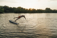 Man jumping from  SUP board on a lake at sunset - GUSF01827