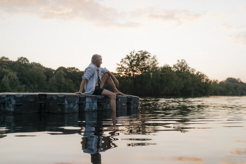 Senior man sitting on raft in a lake at sunset - GUSF01830