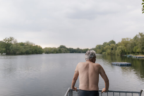 Senior man standing at a lake - GUSF01833